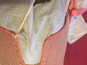 On one side of the bodies, at the top of the centre front, tie the ribbon or laces to one of the eyelet holes.